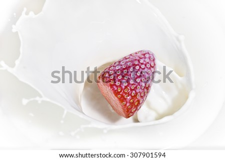 The strawberry falling in milk - stock photo