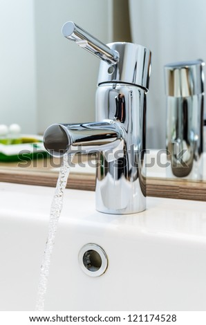 The stream of water from a tap. ceramic washbasin - stock photo