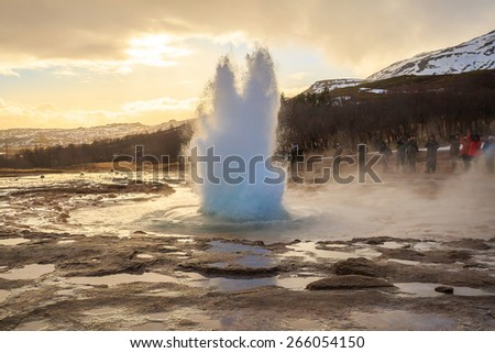The Strokkur geyser in Iceland is erupting at sunset - stock photo