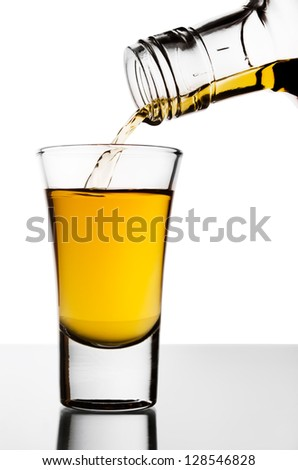 The strong alcohol flowing from a bottle - stock photo