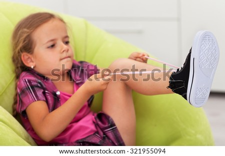 The struggle - cute little girl concentrated to tie shoe, focus on the feet - stock photo