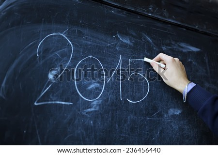 the student writes on a board with a white chalk - 2015 - stock photo