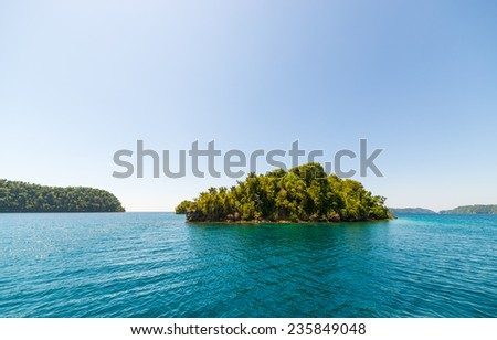 The stunning colors of the sea in the remote Togean Islands (or Togian Islands), Central Sulawesi, Indonesia. Desert islet covered by dense jungle. - stock photo