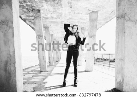 The stylish girl stands on the pier