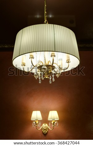 the stylish magnificent chandelier weighing on a ceiling - stock photo