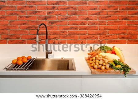 The stylish modern mixer with a sink and vegetables on a kitchen table - stock photo