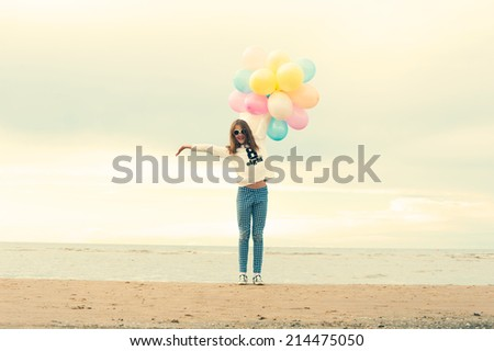 The summer is over. Cheerful young girl with colored balloons on the beach. Outdoors with instagram filter. - stock photo