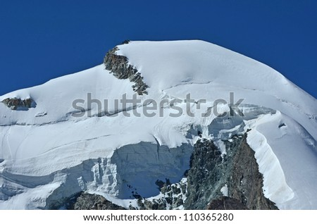 the summit and north face of the Allalinhorn in the southern swiss alps between Zermatt and Saas Fee. Showing a team of climbers on the summit