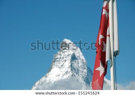 The summit of the Matterhorn with Swiss flag at Sunnegga - stock photo