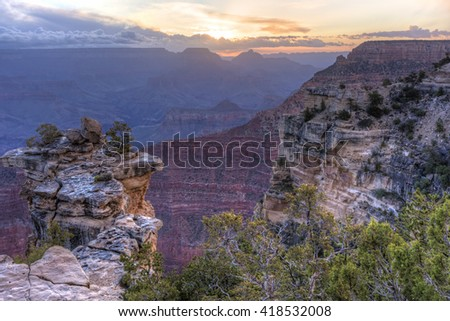 The sun about the break through the clouds in the East from Mather Point in Grand Canyon National Park, Arizona. - stock photo