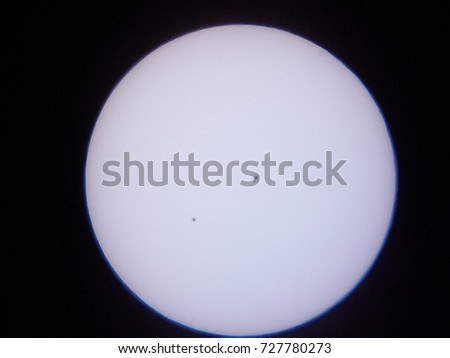 the sun and sunspots through a solar filter on an amateur telescope