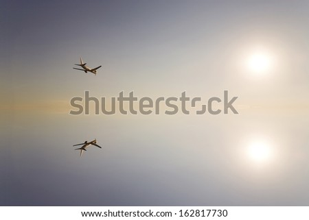 The sun and the passenger plane which are reflected in the water surface - stock photo