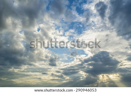 The sun breaking through dark storm clouds with sky background
