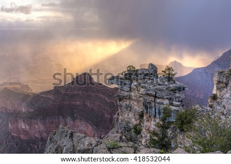The sun breaks through the clouds and snow showers in Grand Canyon National Park, Arizona. - stock photo