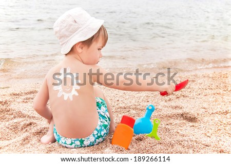 The sun drawing sunscreen (suntan lotion) on baby (boy)  back. Caucasian child is sitting with plastic container of sunscreen and toys on sunny beach. Close up, outdoor (Sharm El Sheikh, Egypt).  - stock photo