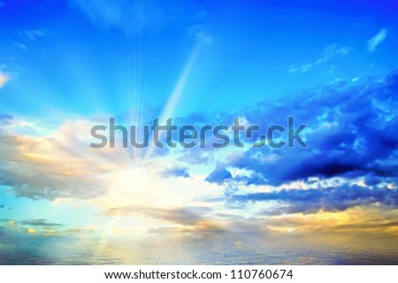 The sun has ascended over the sea and shines because of clouds. - stock photo