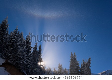 The sun illuminates a cloud of fine ice particles. Winter rainbow in the mountains.