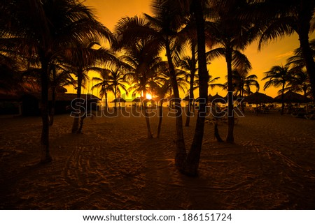 The sun is setting across the ocean waters of Palm Beach in the town of Noord. - stock photo