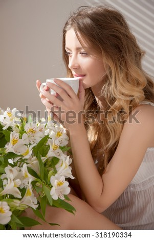 The sun is shining into the bedroom,she looks out the window.Hand and cup.The lady sitting beside the bed,her hand near her head,she looks into the camera.Morning coffee,enjoyment, she closed her eyes - stock photo