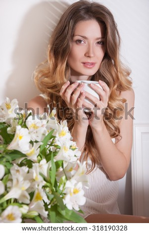 The sun is shining into the bedroom, she looks out the window.Morning with a cup in female hands.lady sitting beside the bed, her hand near her head, she looks into the camera.Morning coffee,enjoyment - stock photo
