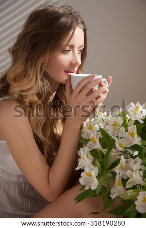 The sun is shining into the bedroom, she looks out the window.Woman and flowers.The lady sitting beside the bed, her hand near her head, she looks into the camera. Morning coffee, enjoyment - stock photo