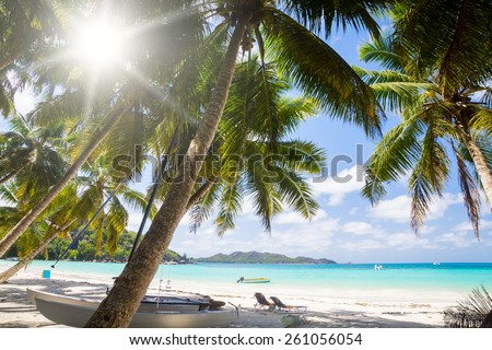 The sun loungers under parasols on solaceon the beach. Rest in the hotel in the Seychelles. - stock photo