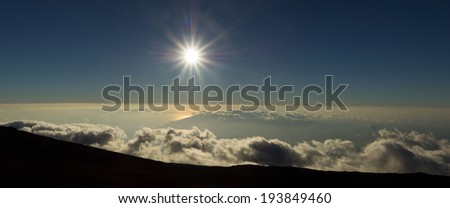 The sun prepares to set over West Maui as seen from Haleakala Crater - stock photo