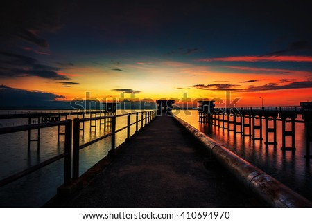 The sun reflected off the bridge that stretches into the sea.In Chonburi Thailand. - stock photo
