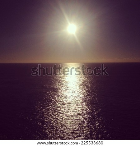 The sun reflects across the ripples of a sea. - stock photo