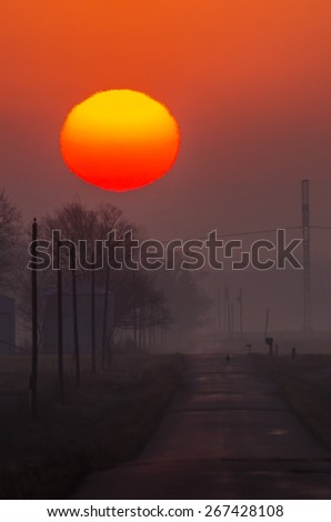 The sun rises above the trees and grain bins along a rural road, on a foggy morning - stock photo