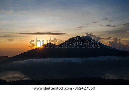 The sun rises at dawn from behind the mountains of Bali. Batur Volcano. Indonesia. Stock image. - stock photo