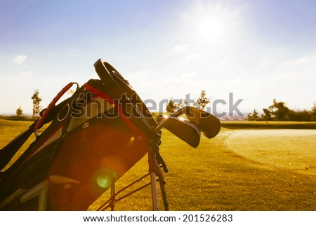 The sun rises due to golf course, bag
