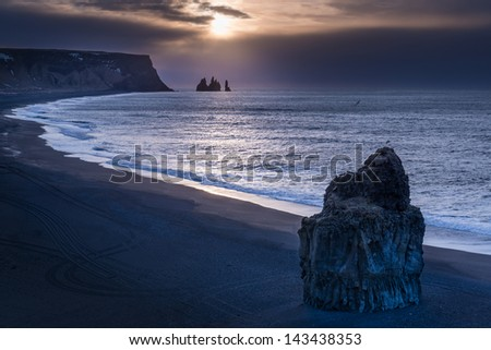 The sun rises over the black beach and rock stacks near Vik, Iceland.