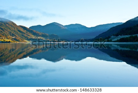 The sun rises over the mountains and its first rays light the lake shore and dissipate the fog, Oppheim, Norway. - stock photo