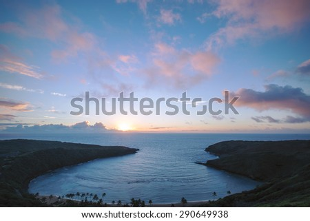 The sun rising over a beautiful bay as seen from a high vantage point on a mountain on the eastern shore of Oahu, Hawaii.  - stock photo