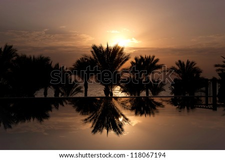 The sun rising over infinity pool, palm trees and Red Sea, Sharm el Sheikh, Egypt - stock photo