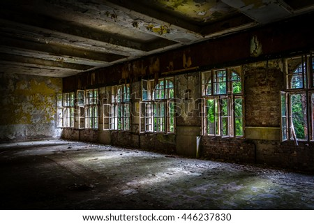 The sun's rays break the darkness in an abandoned destroyed room of an ancient building - stock photo