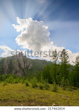The sun's rays from the cloud. Sayan mountains. Summer landscape - stock photo