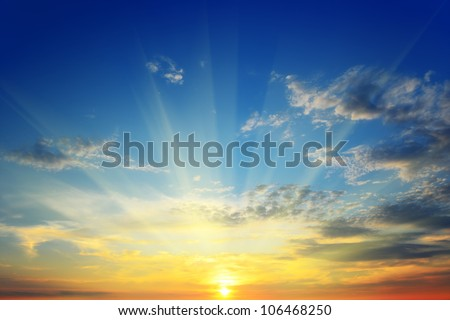 the sun's rays illuminate the sky above the horizon - stock photo