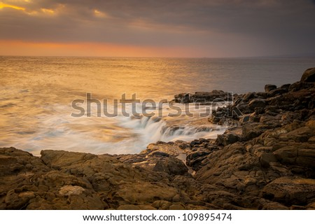 The sun sets as water pounds against the lava shoreline and pours back into the ocean.