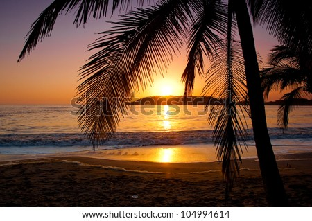 The sun sets behind a little island in Playa Carrillo, Costa Rica. - stock photo