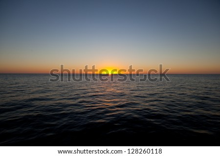 The sun sets on the calm, warm waters of the Caribbean Sea.  The Caribbean has the highest marine diversity in the Atlantic Ocean. - stock photo