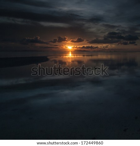 The sun sets over beach with beautiful reflection - stock photo