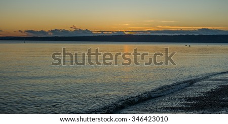 The sun sets over the smooth waters of the Puget Sound near Seattle, Washington. - stock photo
