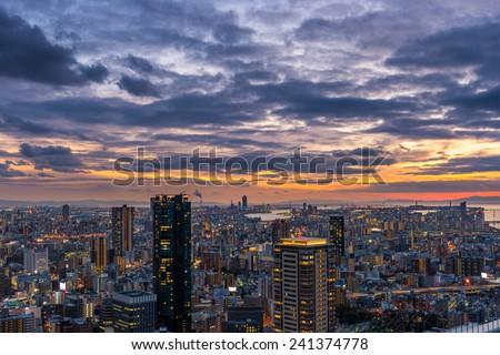 The sun sets over the vast cityscape of Osaka, Japan. - stock photo