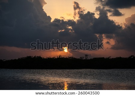 The sun sets over Turneffe Atoll off the coast of Belize in the Caribbean Sea. This tropical area is known for its beautiful scuba diving, snorkeling, and excellent fishing. - stock photo