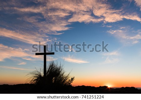 The sun setting behind a black cross