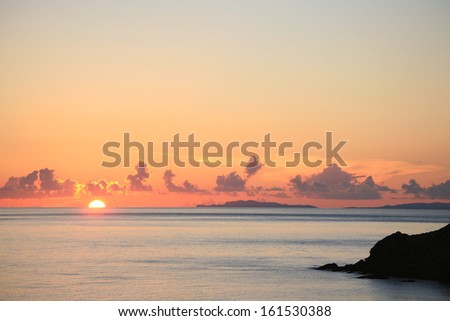 The sun setting by the ocean and some islands. - stock photo