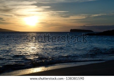The sun setting over the ocean at Big Beach on the Island of Maui. The island Kahoolawe is in the background.