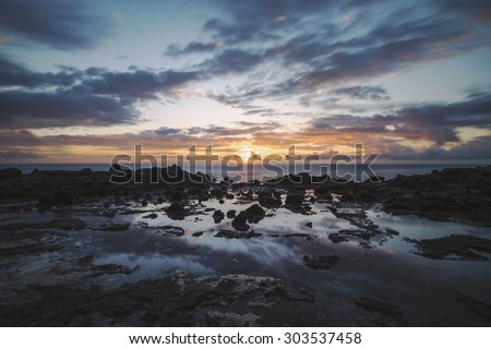 The sun setting over the ocean seen from a rocky shore with tide pools in the foreground. The sunset and colors in the sky reflecting off of the tide pool.  - stock photo
